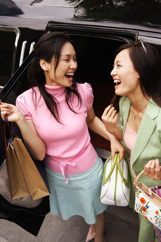 Excited Young Women With Shopping Bags in Front of Limousine