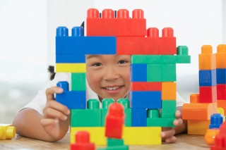 Girl playing with interlocking buildlings blocks