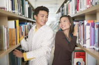Couple looking at each other next to bookshelves