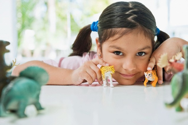 Girl with toy dinosaurs
