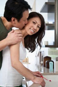 Middle-aged couple snuggling in bathroom