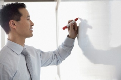 Business man writing on a white board