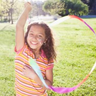Portrait of girl (7-9) playing with streamer in park