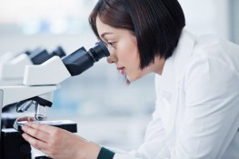 Young technician looking through microscope in laboratory