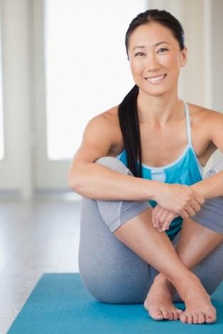 Mid adult woman meditating at home