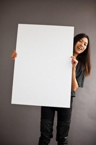 Woman holding blank white board