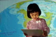 Young girl with tablet in front of a projection of a globe.