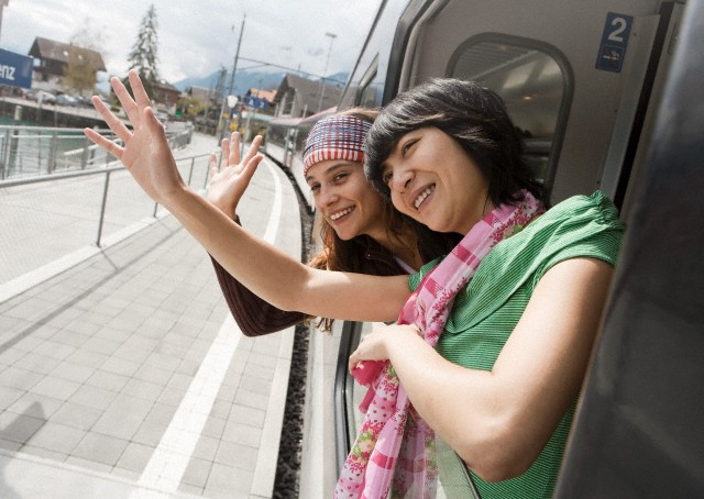 Two women waving out of train window