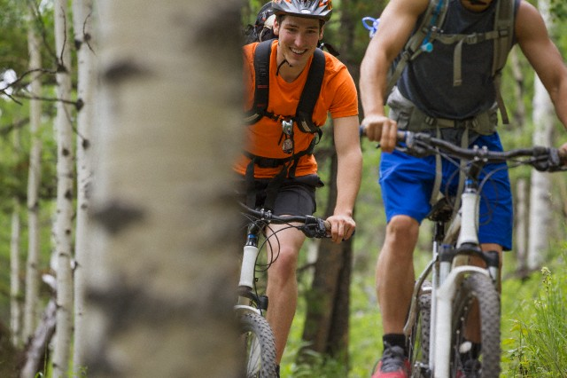 Mountain bikers riding in the woods together.
