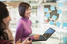 Businesswoman smiling while holding laptop by glass wall.