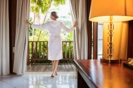 Woman in bathrobe standing in terrace door