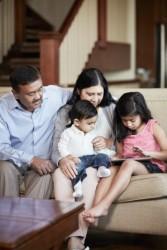 Grandparents with grandchildren (2-3, 6-7) sitting on sofa
