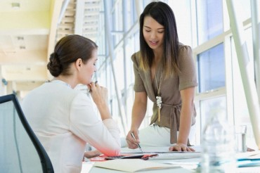 Female business colleagues in conversation at desk.