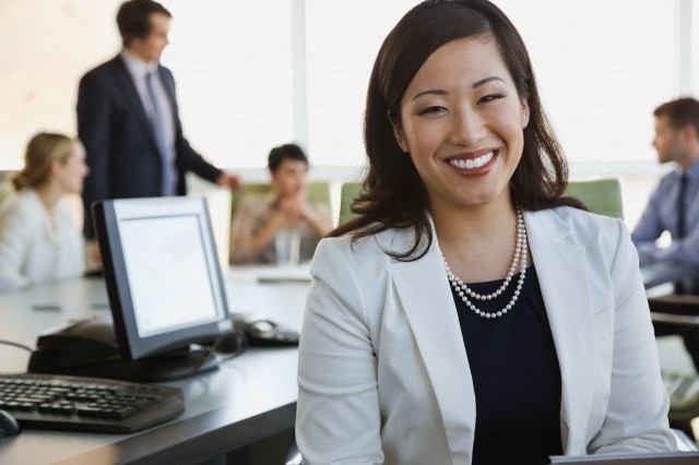 Portrait of businesswoman with colleagues in boardroom.