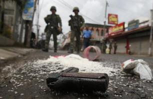 A weapon concealed in a bag of rice carried by a rebel lies on a road in downtown Zamboanga
