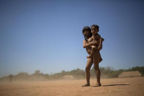 A Waura Indian girl carries a smaller child during this year's 'quarup' in Xingu National Park