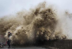 A man dodges tidal waves under the influence of Typhoon Usagi in Hangzhou