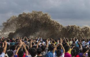 Visitors take pictures of tidal waves under the influence of Typhoon Usagi in Hangzhou