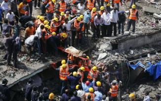 Rescue workers use a stretcher to carry a woman who was rescued from the rubble at the site of a collapsed residential building in Mumbai