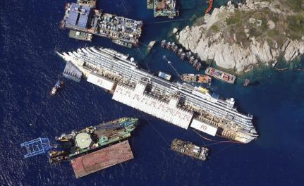 An aerial view shows the Costa Concordia as it lies on its side next to Giglio Island taken from an Italian navy helicopter