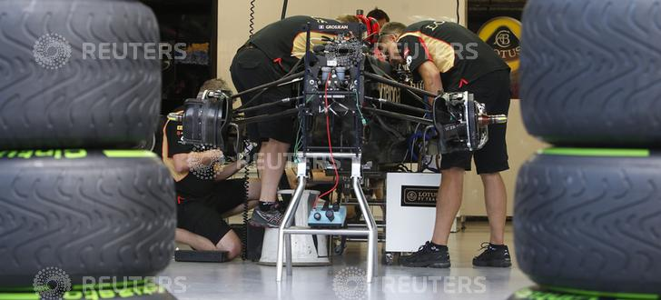 Mechanics work on the car of Lotus Formula One driver Grosjean at the pit ahead of the Singapore F1 Grand Prix