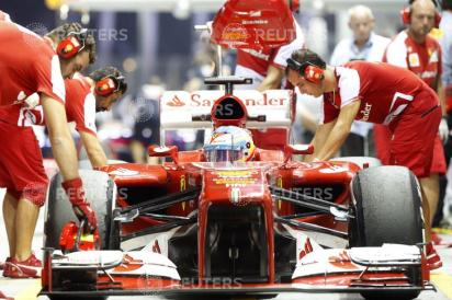 Team members work on the car of Ferrari Formula One driver Alonso during the second practice session of the Singapore F1 Grand Prix in Singapore