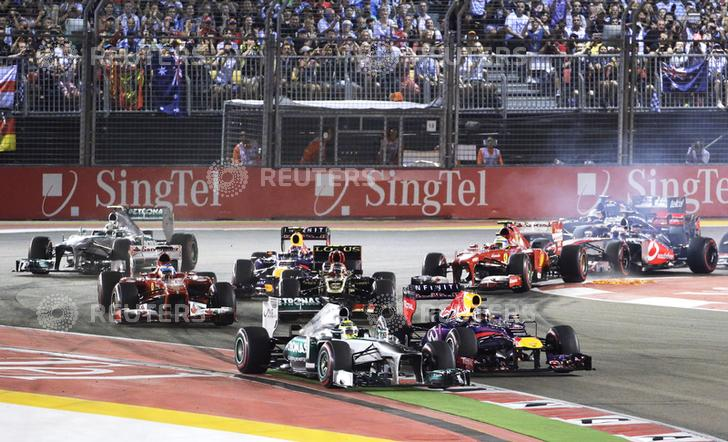 Mercedes Formula One driver Rosberg leads Red Bull Formula One driver Vettel on turn one of lap one during the Singapore F1 Grand Prix in Singapore