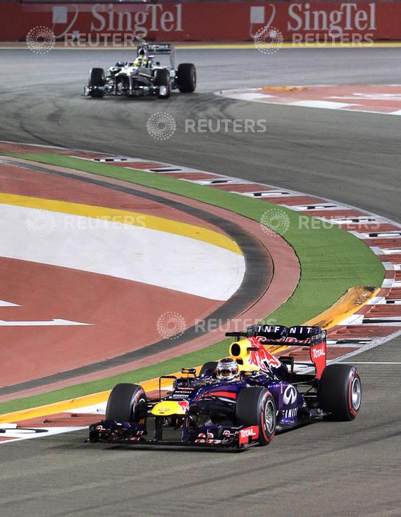 Red Bull Formula One driver Vettel leads Mercedes Formula One driver Rosberg on lap two of the Singapore F1 Grand Prix in Singapore