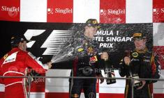 Ferrari Formula One driver Alonso sprays champagne at Red Bull Formula One driver Vettel and Lotus F1 Formula One driver Raikkonen on the podium after the Singapore F1 Grand Prix in Singapore