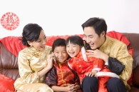 Family in traditional clothes sitting on sofa and smiling happily