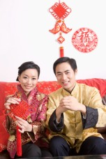Young man with hands clasped and young woman holding a Chinese decoration, smiling at camera together