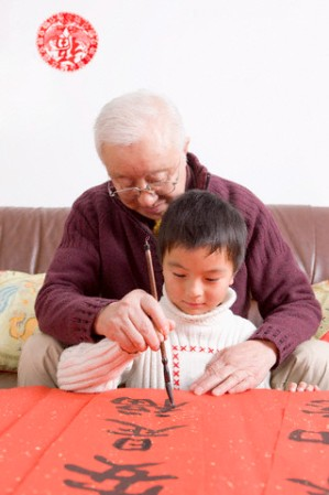 Senior man teaching little boy to write Chinese scripts