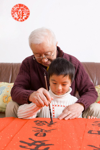 Senior man teaching little boy to write Chinese scripts