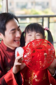Young father holding decoupage and smiling happily with little girl