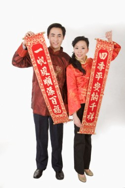 Young couple in traditional clothes holding couplets and smiling at camera