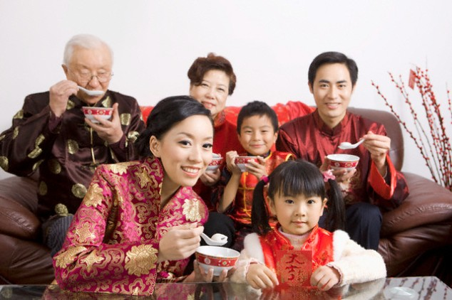 Whole family in traditional clothes eating dumplings