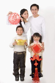 Young family with two children holding decorations to celebrating Chinese New Year