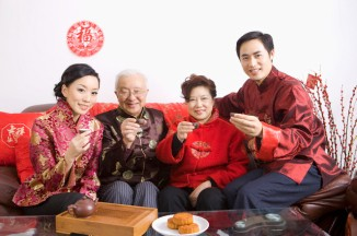 Family members in traditional clothing holding teacups and smiling at camera