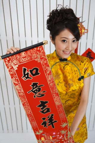 Young woman wearing Chinese traditional clothing and holding the couplet with smile