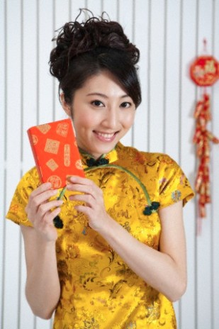 Young woman wearing Chinese traditional clothing and holding a gift with smile