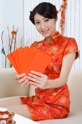 Young woman wearing Chinese traditional clothing and holding red envelopes with smile
