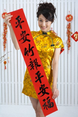 Young woman wearing Chinese traditional clothing and holding couplet with smile