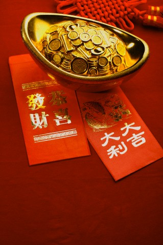 Close up of red envelopes and a gold ingot