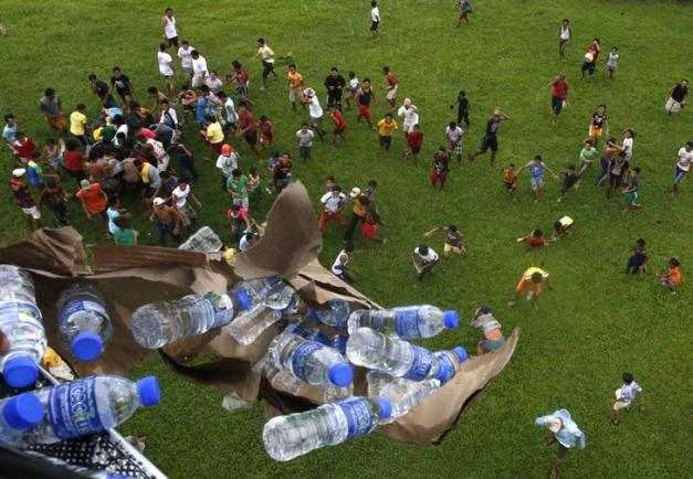 A Philippine military helicopter drops bottled water to Typhoon Haiyan survivors in Tolosa