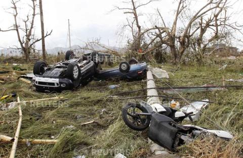 Overturned vehicles are seen at a rice field after super Typhoon Haiyan battered Tacloban city