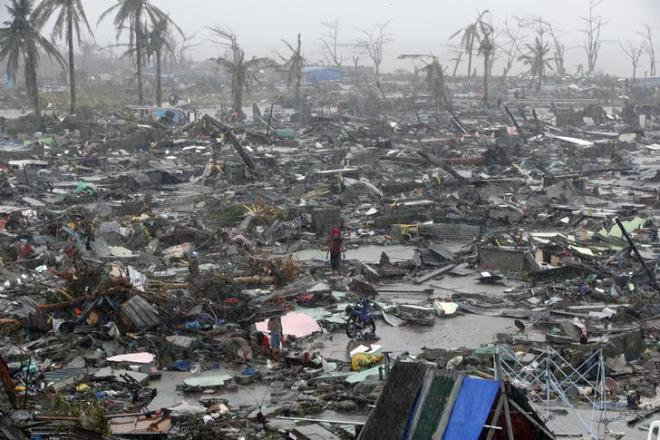People stand among debris and ruins of houses destroyed after Super Typhoon Haiyan battered Tacloban city in central Philippines