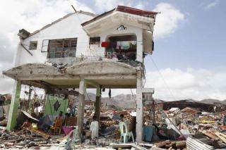 Survivors stay in their damaged house after super Typhoon Haiyan battered Tacloban city