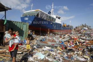 Residents walk past a cargo ship washed ashore four days after super typhoon Haiyan hit Tacloban
