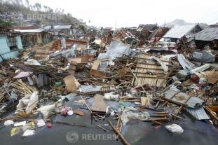 Devastated houses float on sea water after super typhoon Haiyan hit Tacloban
