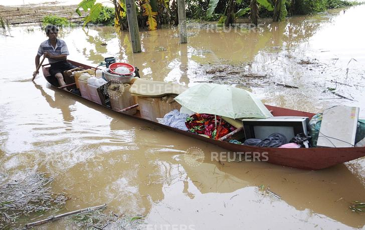 A man rows a boat carrying his belongings through flood waters due to typhoon Haiyan in Shangsi